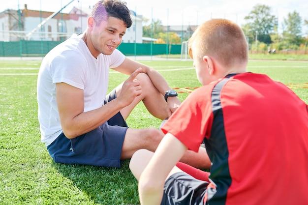 Treinador de esportes conversando com o menino