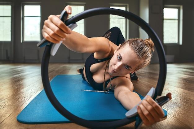 Treinador de fitness com uma bela figura posa para a câmera durante um treino na academia