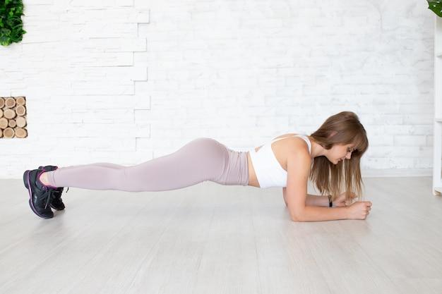 Treinador de fitness fazendo prancha para fortalecer seus bíceps, tríceps e abdominais. conceito de esporte feminino.