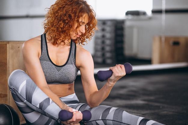 Treinador de fitness mulher com halteres no ginásio