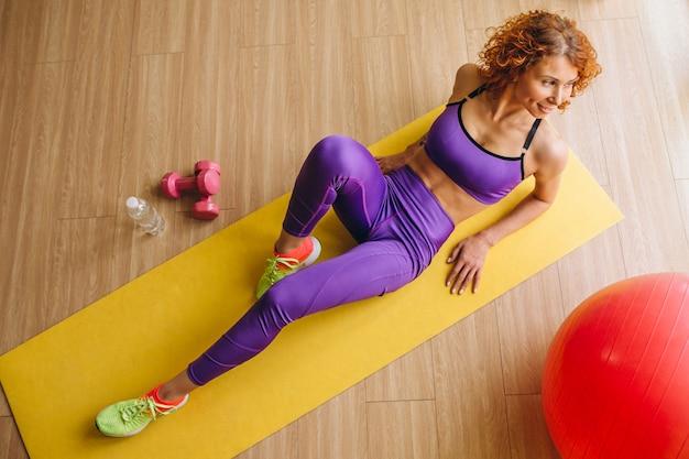 Treinador de fitness mulher deitada na esteira