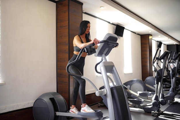 Treinador de fitness trabalhando na máquina de passo e mostrando sua figura em um terno de esportes