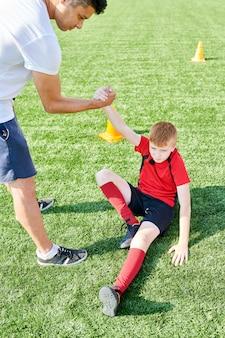 Treinador de futebol ajudando menino