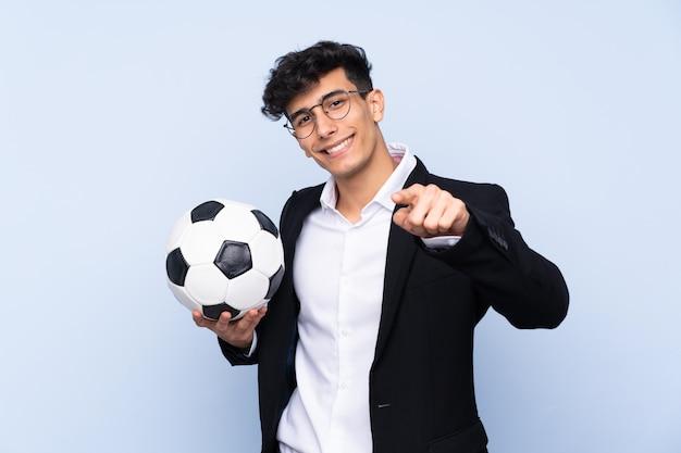 Treinador de futebol argentino sobre parede azul isolada aponta o dedo para você com uma expressão confiante