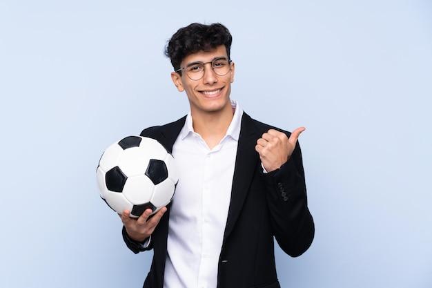 Treinador de futebol argentino sobre parede azul isolada, apontando para o lado para apresentar um produto