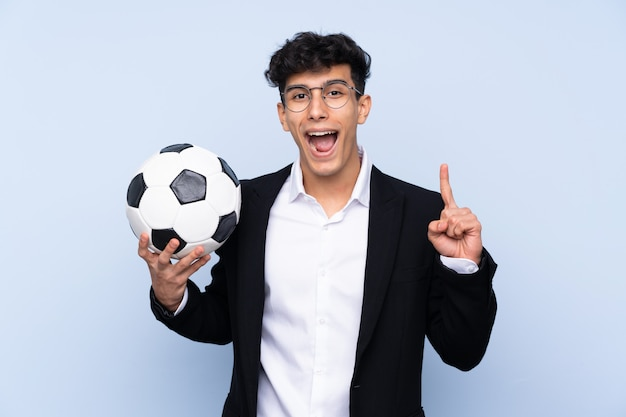 Treinador de futebol argentino sobre parede azul isolada apontando uma ótima idéia
