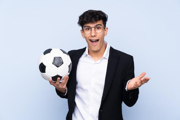 Treinador de futebol argentino sobre parede azul isolada com expressão facial chocado
