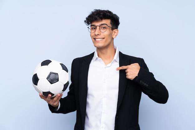 Treinador de futebol argentino sobre parede azul isolada com expressão facial de surpresa