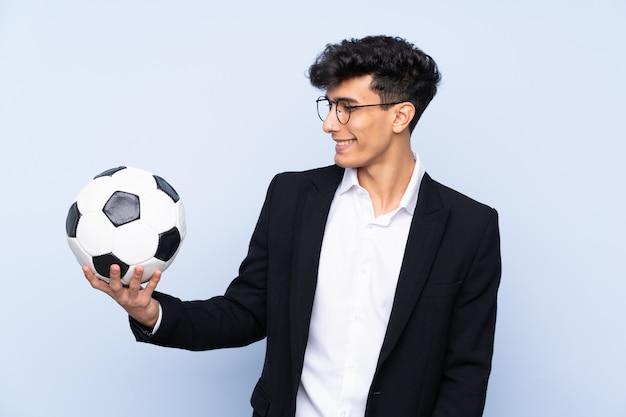 Treinador de futebol argentino sobre parede azul isolada com expressão feliz
