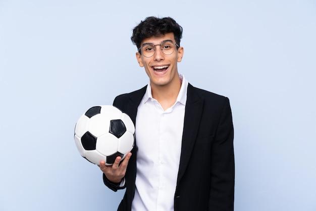 Treinador de futebol argentino sobre parede azul isolada com surpresa e expressão facial chocado