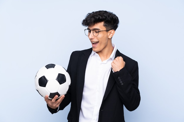 Treinador de futebol argentino sobre parede azul isolada comemorando uma vitória