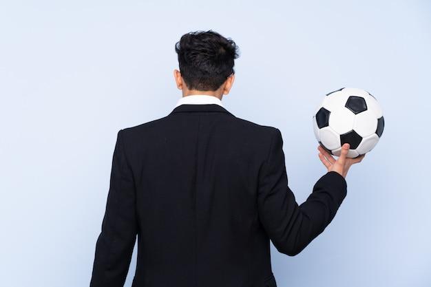 Treinador de futebol argentino sobre parede azul isolada em posição traseira