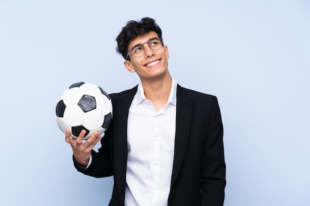 Treinador de futebol argentino sobre parede azul isolada, olhando para cima enquanto sorrindo