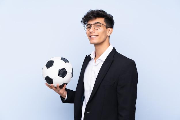 Treinador de futebol argentino sobre parede azul isolada, sorrindo muito
