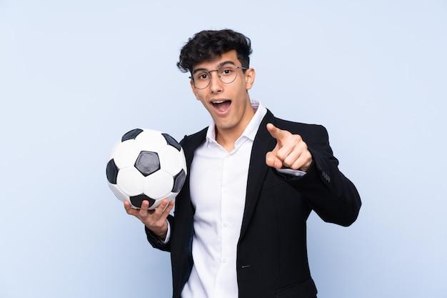 Treinador de futebol argentino sobre parede azul isolada surpreso e apontando a frente