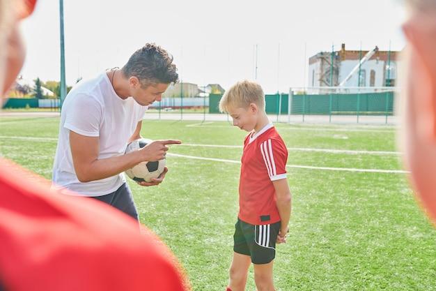 Treinador de futebol, motivando o menino