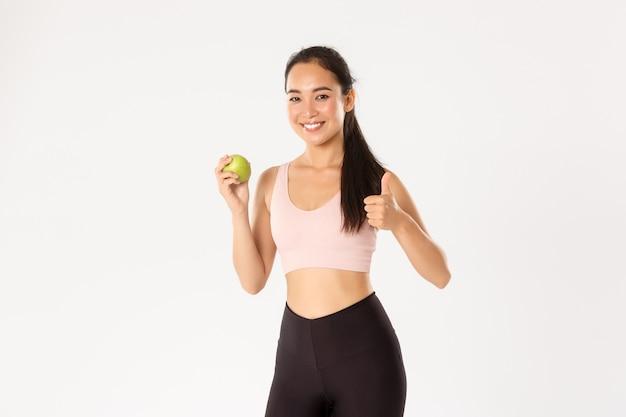 Treinador de ginástica feminino bonito magro e saudável, instrutor de fitness, conselhos sobre como comer vitaminas, mostrando o polegar para cima e maçã verde, sorrindo, recomendando dieta.