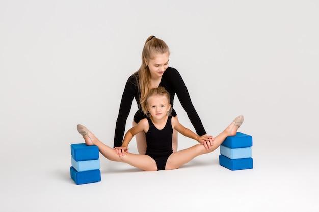 Treinador de ginástica jovem lida com aluna na parede branca