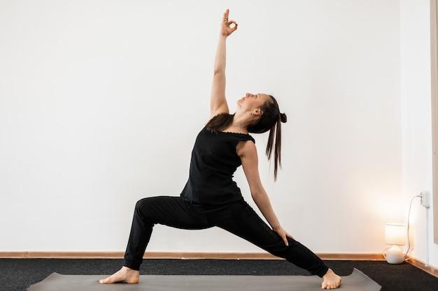 Treinador de jovem fazendo ioga e alongamento. o treinador profissional de garotas mantém o equilíbrio.