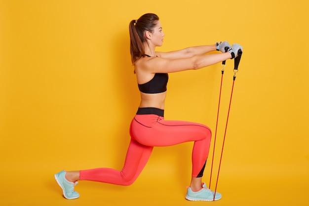Treinador de mulher caucasiana em caneleiras desportivo curto top e vermelho ginásio faz lunges por pés para a frente com expansor de fitness, atleta feminina esticar as pernas com expansor elástico no estúdio de pilates.