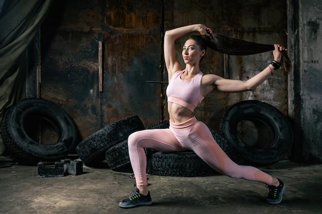 Treinador de mulher desportivo investe com as pernas, fazendo fitness em uma garagem velha. conceito de praticar esportes em condições inadequadas difíceis