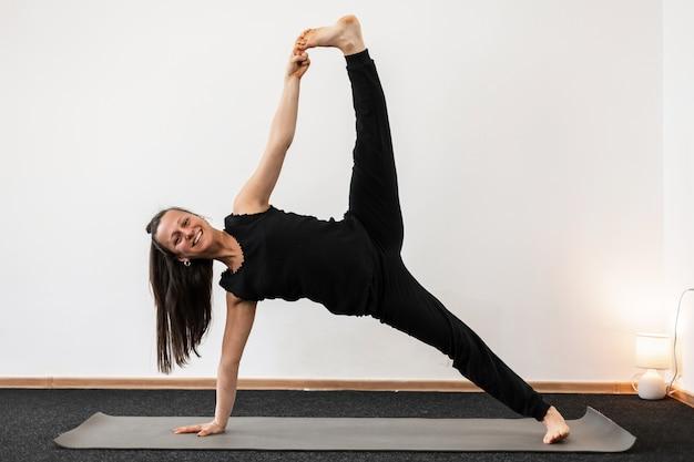 Treinador de mulher jovem feliz fazendo ioga e alongamento. o treinador profissional de garotas mantém o equilíbrio dentro de casa.