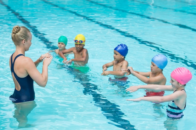 Treinador de natação instruindo alunos na piscina