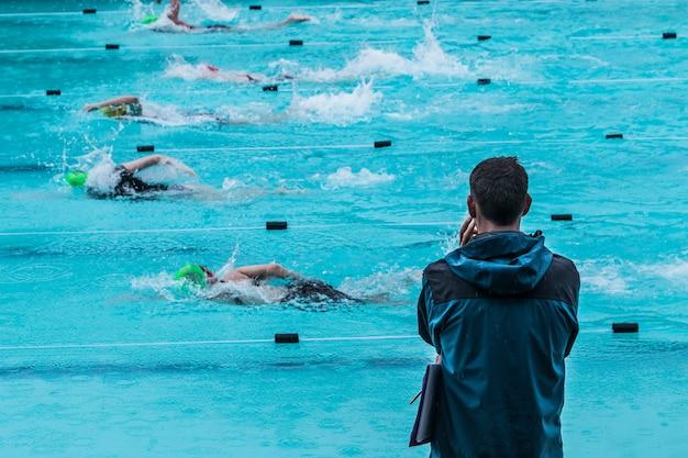 Treinador de natação masculino em pé à beira da piscina na chuva assistindo nadadores correndo por