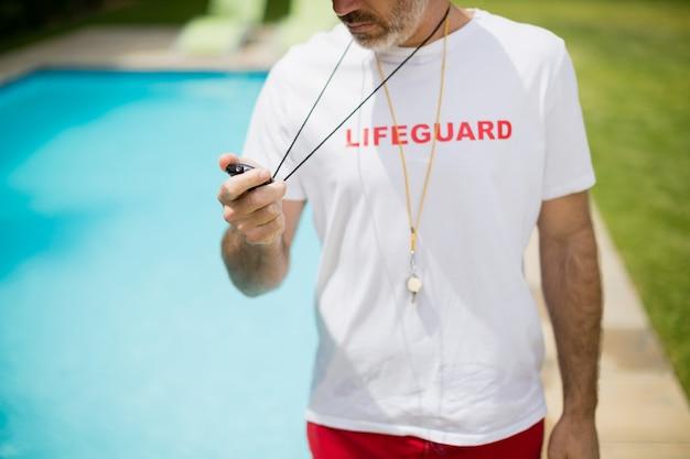 Treinador de natação olhando para o cronômetro perto da piscina em um dia ensolarado