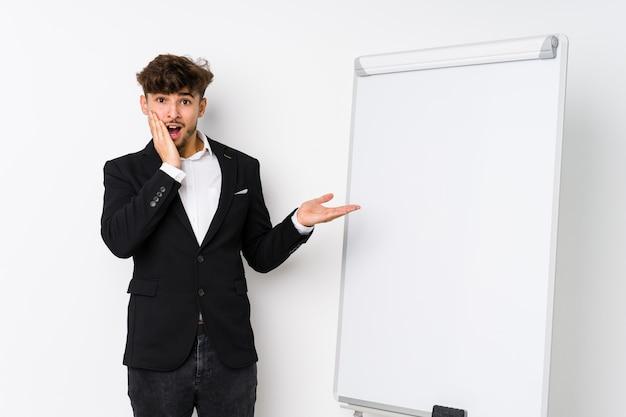 Treinador de negócios jovem homem mantém a mão na bochecha