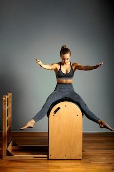 Treinador de pilates exercita em um barril de pilates. treinamento corporal, formato corporal perfeito e correção de postura do aparelho motor opporno. copie o espaço. mulher fazendo exercícios no barril da escada.