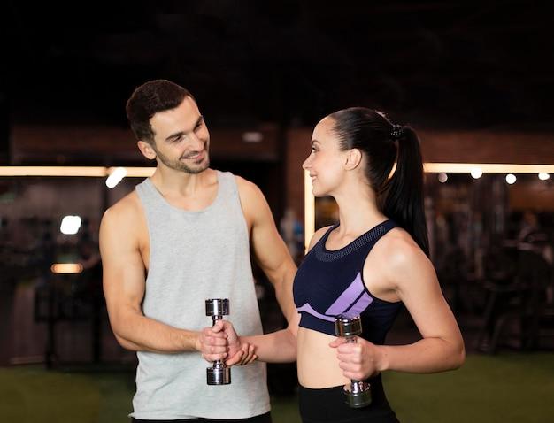 Treinador de tiro médio e mulher na academia