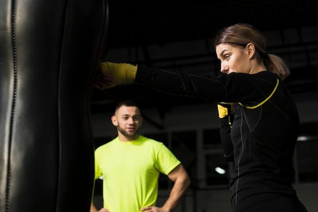Treinador desfocado assistindo boxer feminino praticando no saco de pancadas