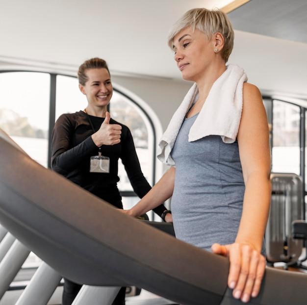 Treinador do programa de exercícios e cliente em pé na esteira