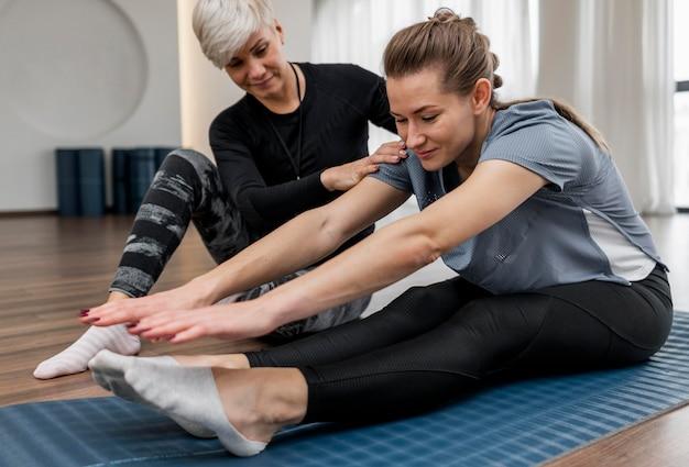 Treinador do programa de treino e cliente fazendo exercícios