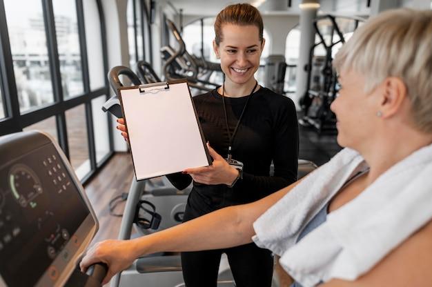 Treinador do programa de treino e cliente mostrando a área de transferência