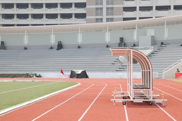 Treinador e bancos de reserva na vista lateral do estádio de futebol