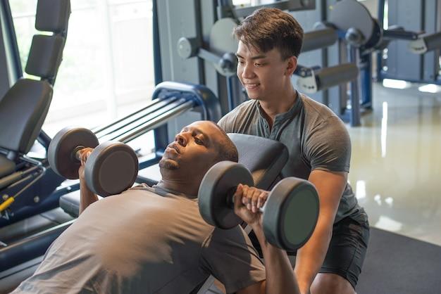 Treinador e homem deitado e levantando halteres no ginásio