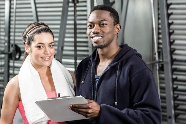 Treinador e mulher olhando para o plano de treino no ginásio
