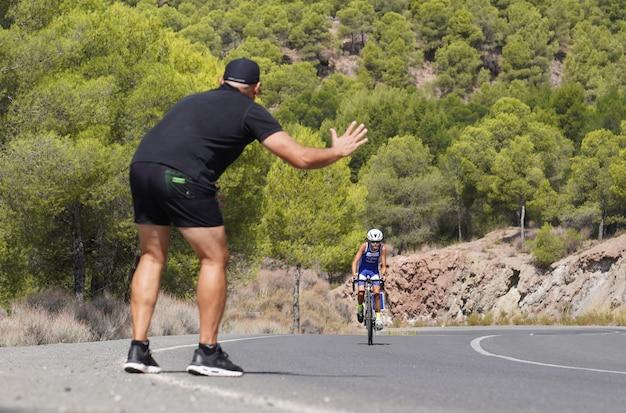 Treinador e pai animando o aluno e o filho em uma corrida de ciclismo