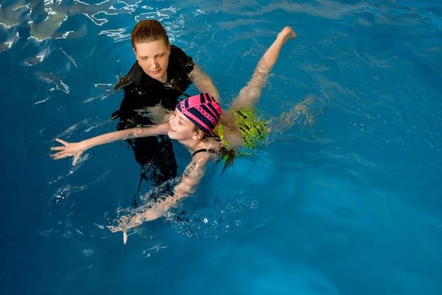 Treinador ensinando criança em piscina coberta a nadar e mergulhar