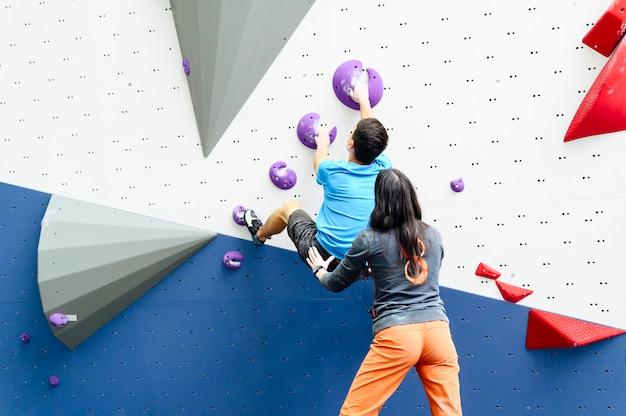 Treinador ensinando escalada em parede de escalada
