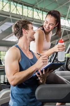 Treinador, escrevendo sobre uma prancheta enquanto mulher exercitando em uma máquina elíptica