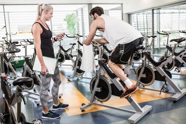 Treinador feminino olhando para cronômetro e homem usando bicicleta ergométrica no ginásio