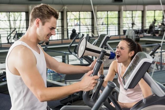 Treinador, gritando através de um megafone enquanto homem exercitando na máquina elíptica