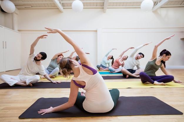 Treinador grupo de pessoas ajudando com exercício de alongamento