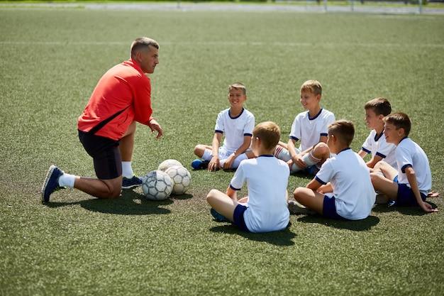 Treinador, instruindo o time de futebol júnior