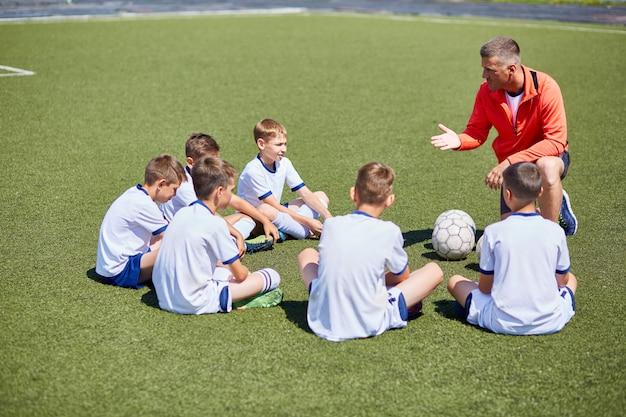 Treinador, instruindo o time de futebol no campo