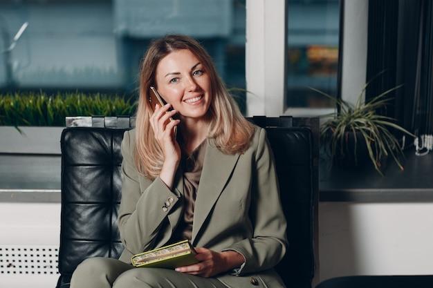 Treinador jovem adulto de mulher de negócios usando o telefone celular na cadeira do escritório