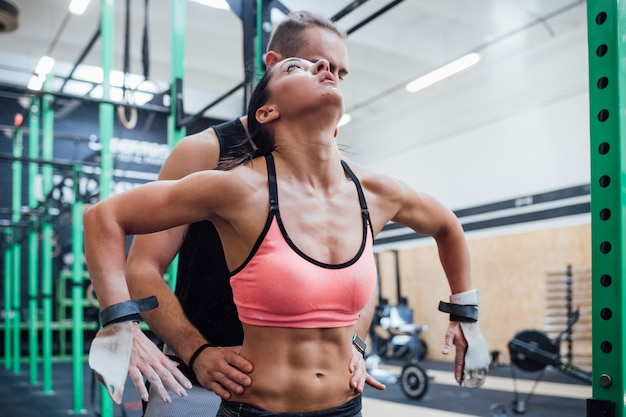 Treinador jovem, ajudando, atleta mulher, alcançar, anel ginástico